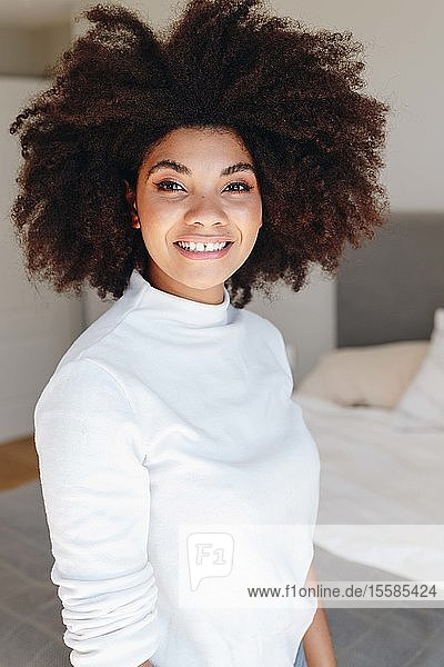 Happy young woman with afro hairstyle in bedroom  waist up portrait