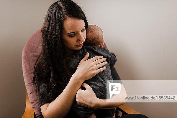 Junge Frau hält kleinen Sohn im Wohnzimmersessel