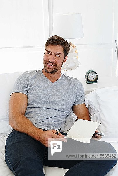 Man using smartphone and writing notes on sofa