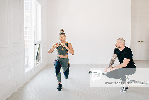Fitnesstrainerin beobachtet Frau beim Ausfallschritt im Studio