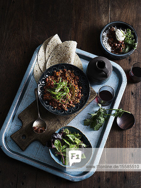 Rustic low key still life with tray of chilli con carne  salad and coffee  overhead view