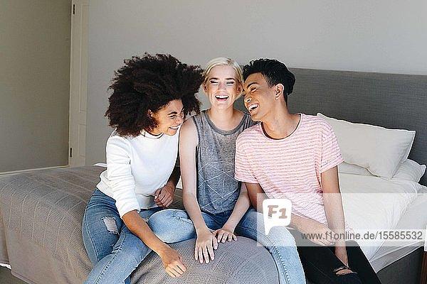Junger Mann und zwei Freundinnen sitzen zusammen im Bett und lachen