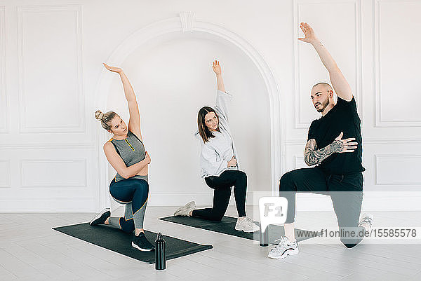 Fitness instructor teaching women stretching arm in studio