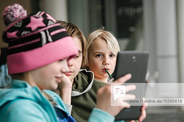 Mädchen und Brüder schauen auf digitales Tablet in Flughafen  Kopf und Schultern