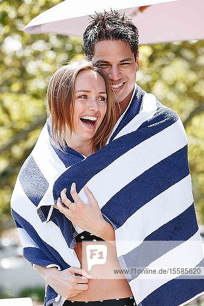 Couple wrapped in striped towel enjoying sun