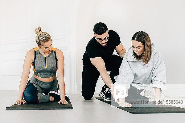 Fitnesstrainerin unterrichtet Frauen beim Beinstrecken im Studio