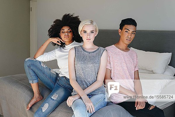 Cooler mittelgroßer Mann und zwei Freundinnen sitzen auf dem Bett  Porträt