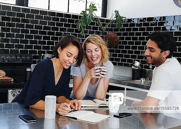 Kollegen sprechen und arbeiten in der Kaffeepause in der Speisekammer
