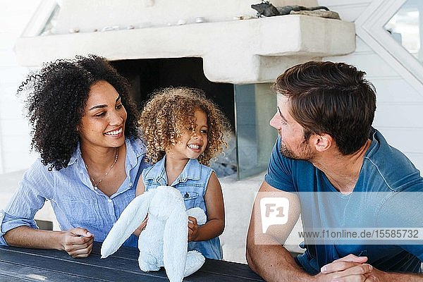 Couple talking and playing with daughter in beach house