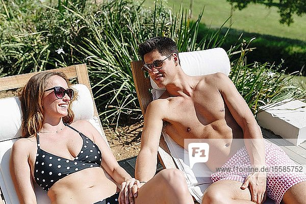 Young couple talking and relaxing on deckchair