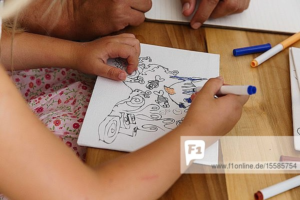 Child colouring a picture on a table