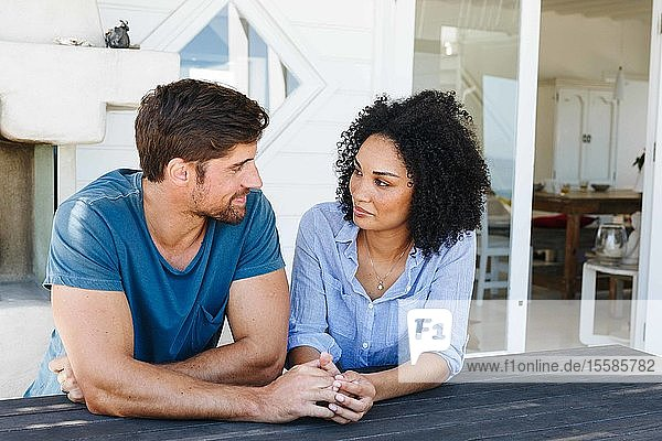 Loving couple staring at each other in beach house