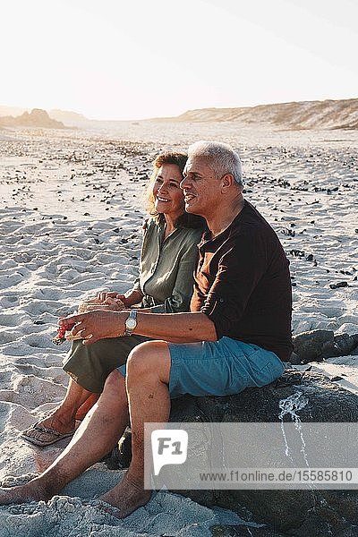 Senior couple enjoying sun on sandy beach
