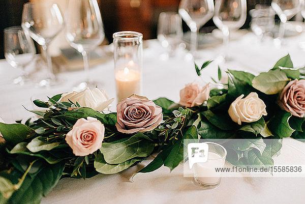 Gedeck am Hochzeitstisch mit Rosengirlandendekoration  Kerzen und Trinkgläsern