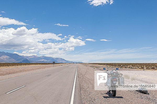 Landschaft mit am ländlichen Straßenrand abgestelltem Motorrad  Mendoza  Argentinien