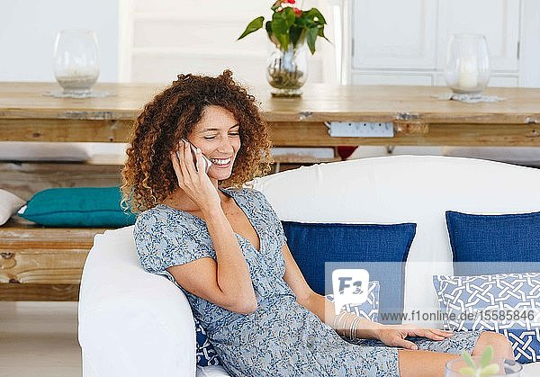 Woman talking on cellphone on sofa