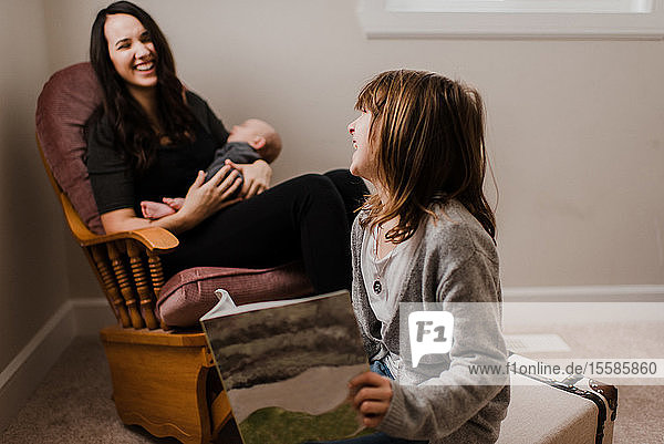 Mädchen  das mit der Mutter lacht  während sie den kleinen Bruder im Wohnzimmersessel wiegt
