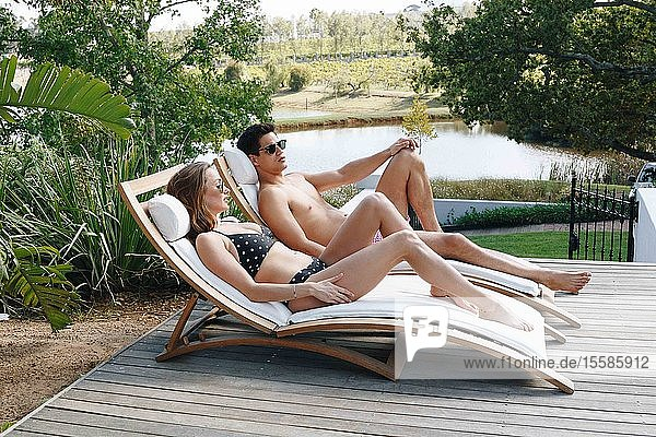 Young couple relaxing on deckchair by pond
