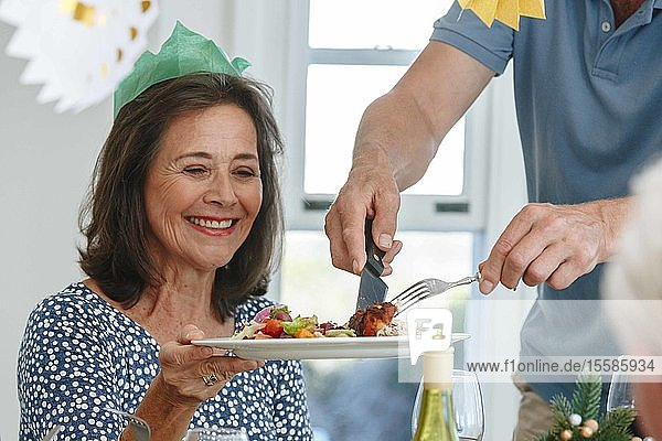 Man serving woman at dining table in home party