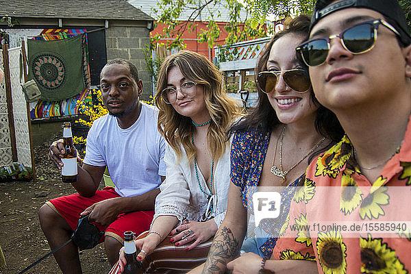 Vier junge erwachsene Freunde entspannen sich auf der Gartenparty der Gemeinde  Seitenansicht Porträt