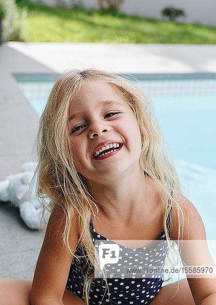 Happy little girl sitting by swimming pool