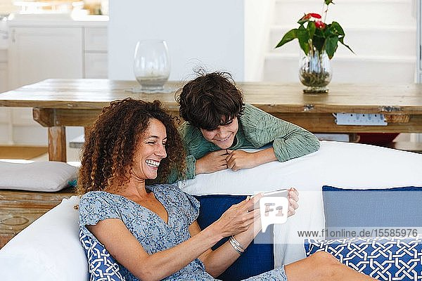 Mother and son smiling at text message on cellphone