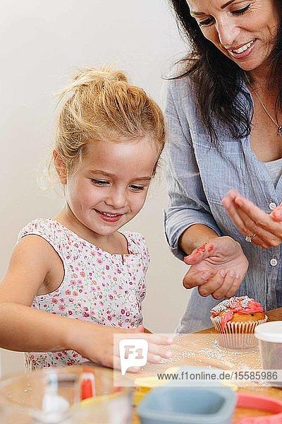 Mutter und Tochter dekorieren Cupcake mit Zuckerguss in der Küche