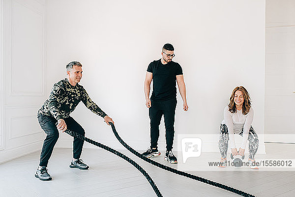 Fitness instructor observing man using battle rope in studio