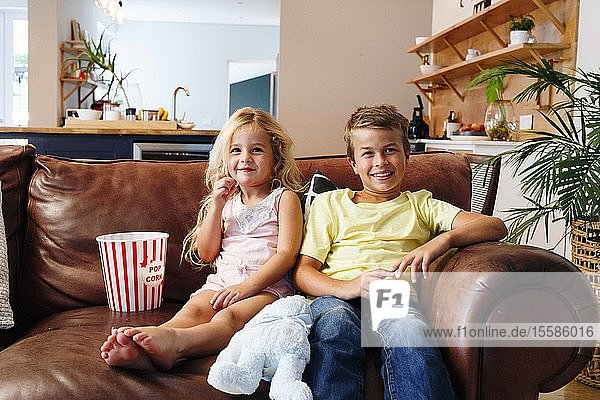 Children relaxing with popcorn on sofa at home