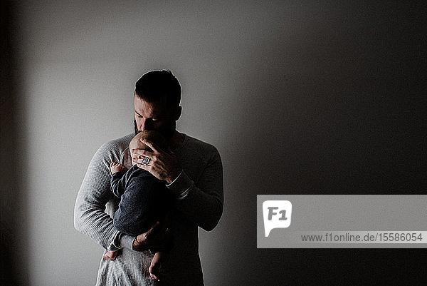 Junger Mann  der seinen kleinen Sohn auf dem Arm trägt