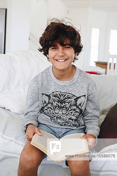 Boy reading book on sofa at home