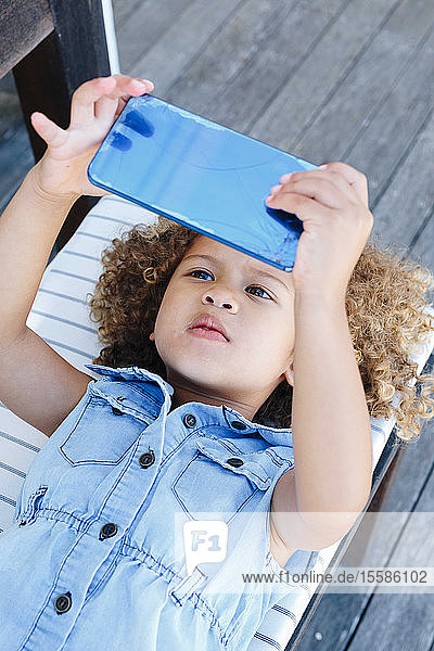 Little girl using smartphone on bench