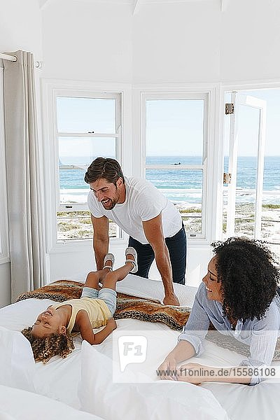Couple playing with daughter in bed in beach house