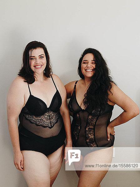 Freunde in Dessous posieren drinnen vor grauem Hintergrund