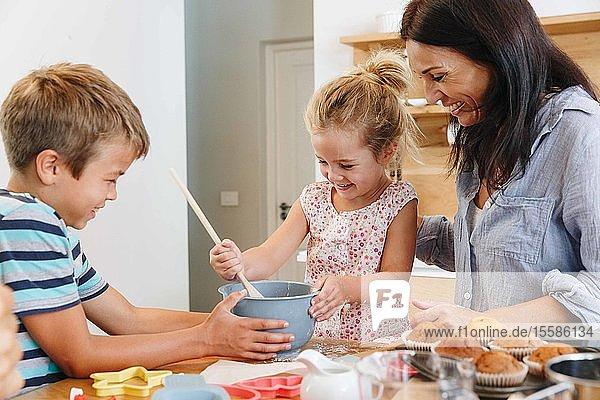Mutter und Kinder backen Cupcakes in der Küche