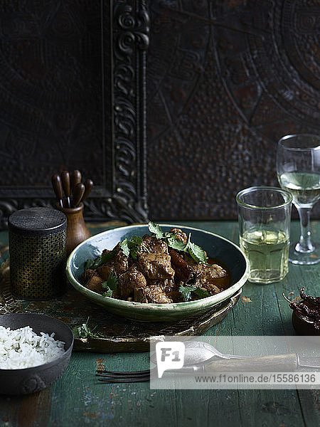 Rustic low key still life with bowl of chettinad black pepper chicken fry and white wine on table