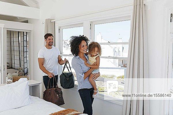 Ehepaar und Tochter verlassen Schlafzimmer im Strandhaus