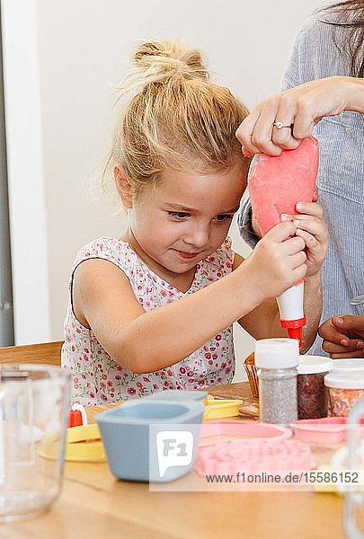 Mother and daughter decorating cupcake with frosting in kitchen