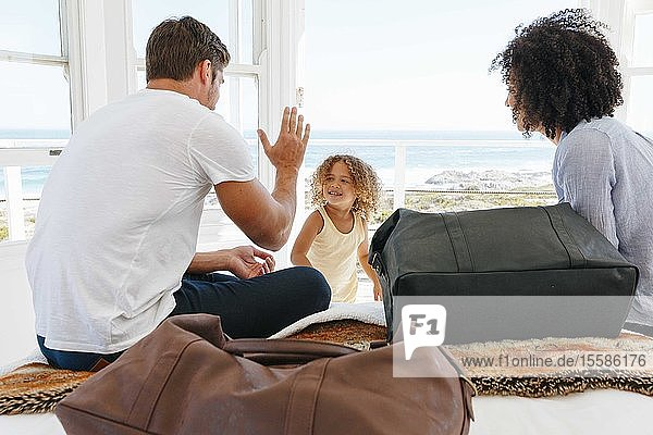 Woman watching husband giving high five to daughter in beach house