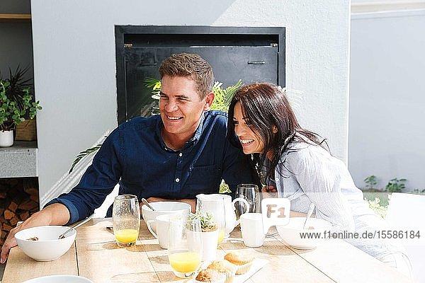Ehepaar beim Mittagessen und Lächeln zu Hause