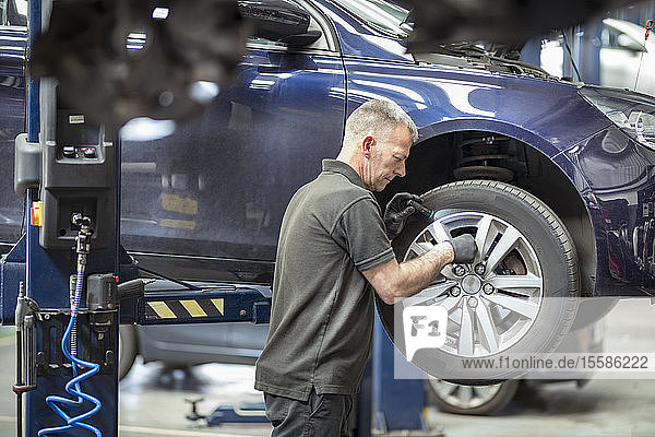 Engineer checking brakes in car service centre