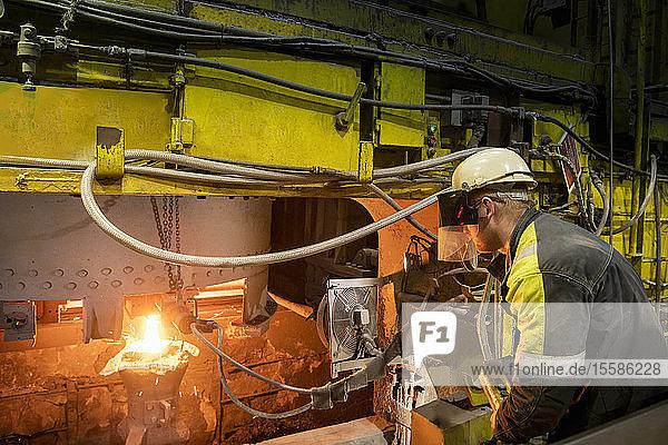 Arbeiter gießt geschmolzenen Stahl aus Kolben in Stahlwerk in Gussformen