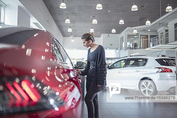 Weibliche Kundin inspiziert neues Auto im Autohaus