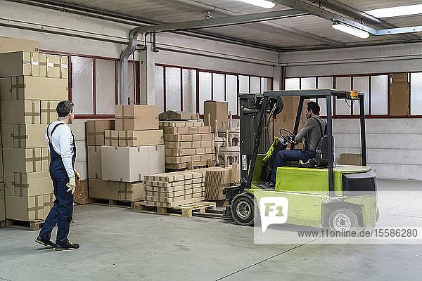 Arbeiter hebt Kistenpaletten mit Gabelstapler in der Fabrik