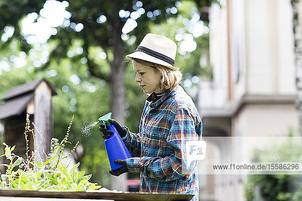 Mid adult woman spraying plants in her garden  side view