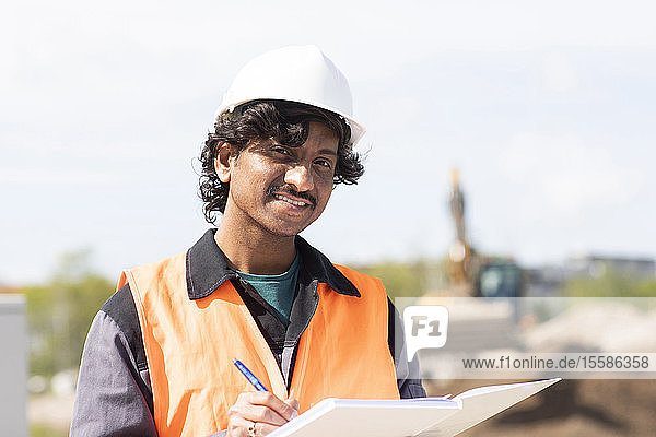 Male engineer on construction site writing in notebook  head and shoulder portrait