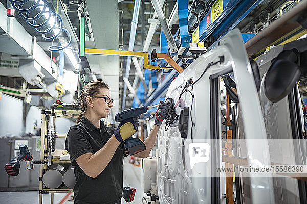 Female worker assembling car doors on production line in a car factory