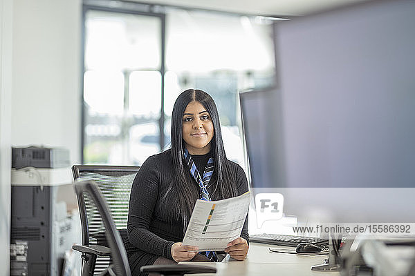 Portrait of female apprentice service advisor in car dealership
