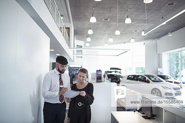 Verkäufer bespricht Vertrag mit Kunde im Autohaus
