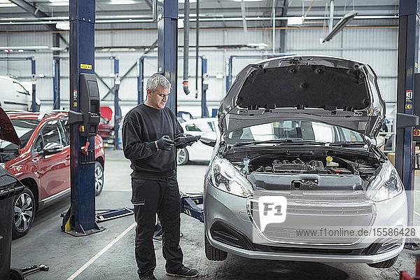 Ingenieur inspiziert Auto in Autowerkstatt